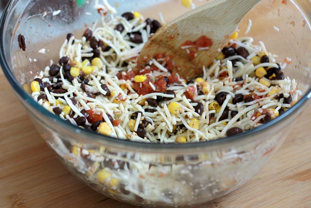 Black beans, shredded cheese, corn and salsa being mixed together in a clear mixing bowl by a wooden spoon.