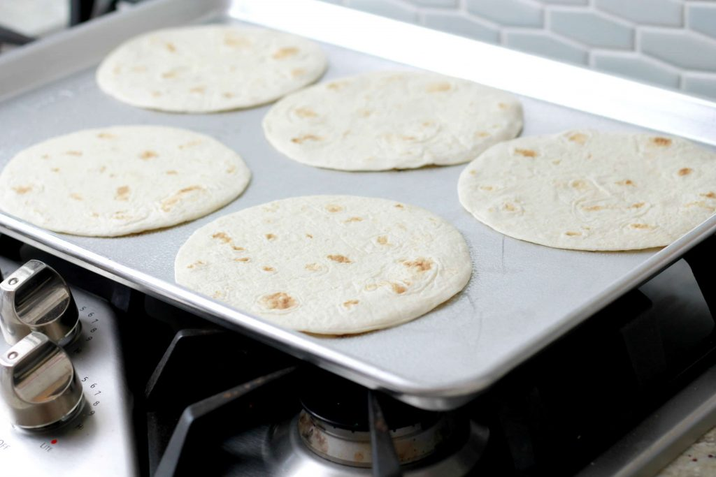 5 four tortillas placed on a sheet pan to heat.