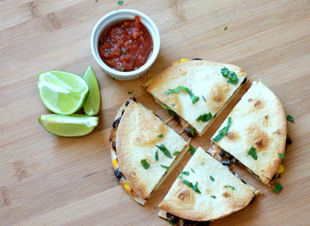 Three corn, black bean, salsa, and shredded cheese quesadillas stacked on top of one another served with a side of salsa and a lime, toed with seasoning, sliced in fours.