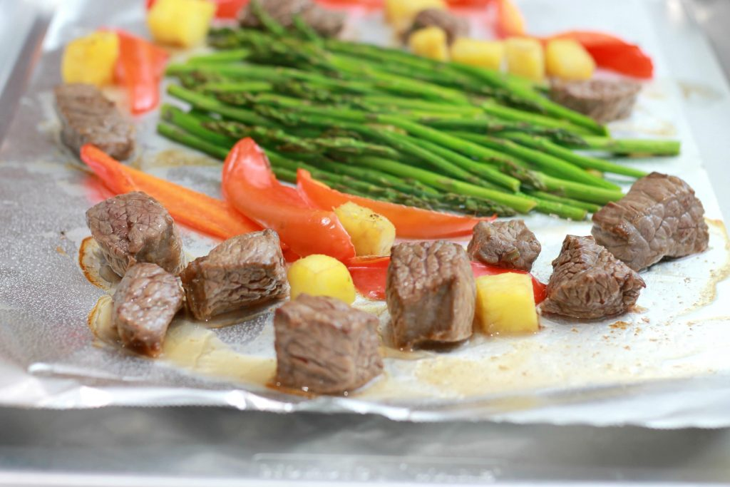 Asparagus, chopped pineapples, sliced red bell peppers, and steak all placed on one pan ready.