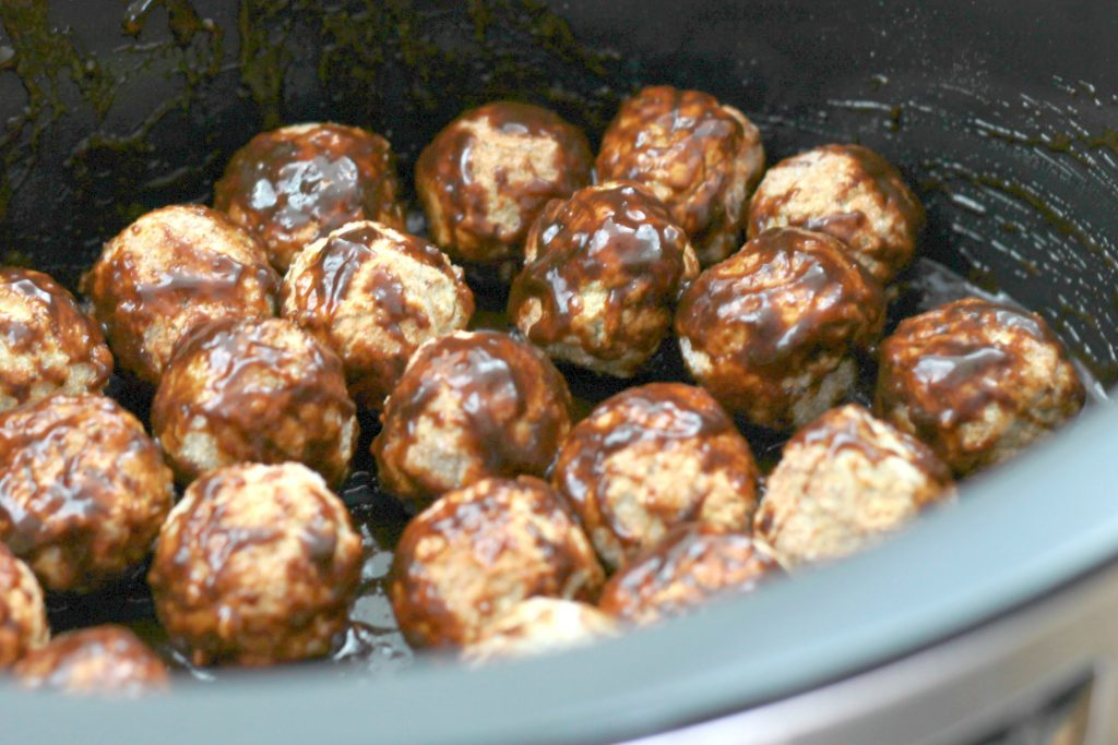 Frozen meatballs topped with sauce and seasoning placed in a crock pot ready to be slow cooked.