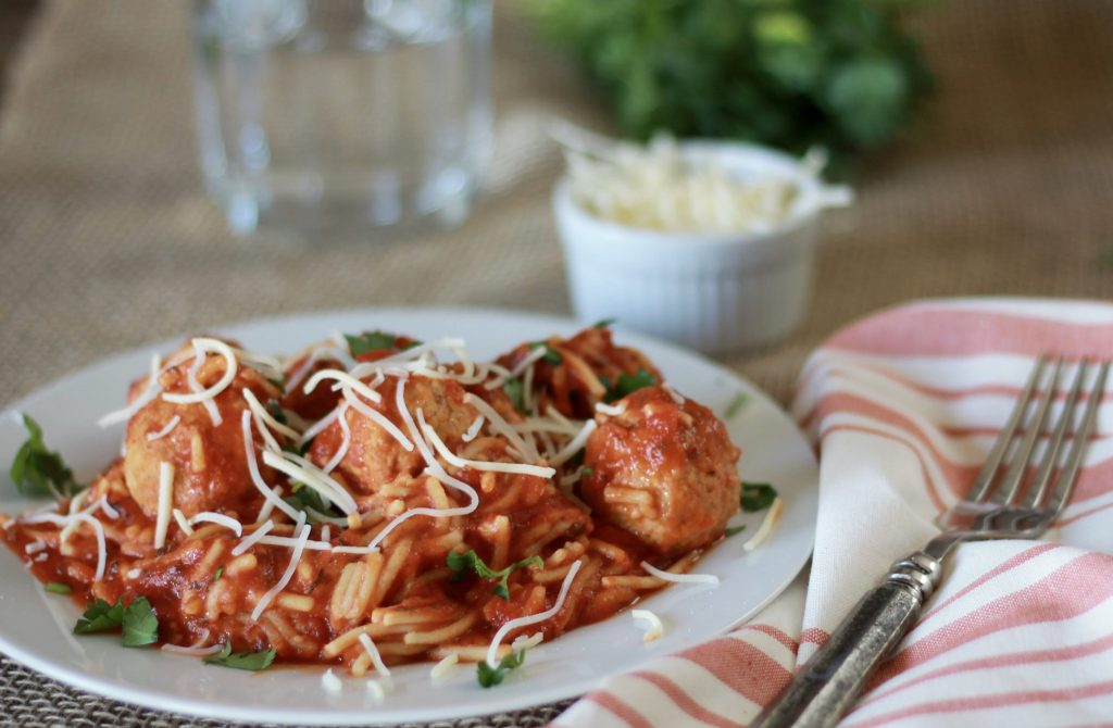 Gluten free multi grain spaghetti pasta with sauce and meatballs served with shredded cheese on a plate ready to be eaten.