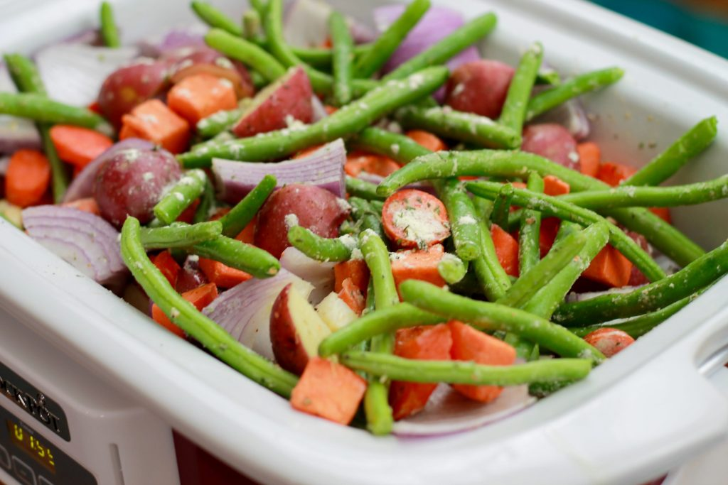 Fresh green beans, onions, petite tomatoes and carrots all mixed together in a slow cooker.