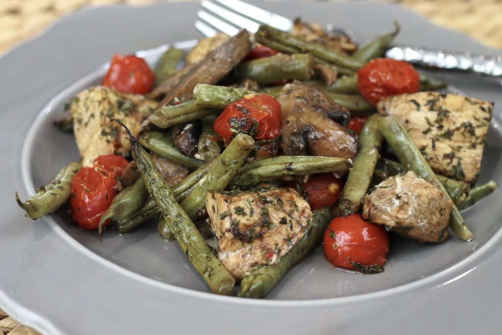 One pan dinner of balsamic chicken, green bean, petite tomatoes served on a grey plate ready to be eaten.