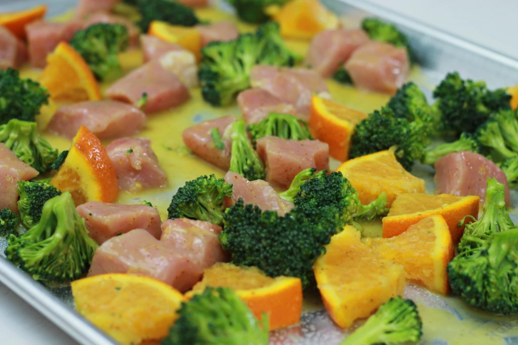 One pan dish ready to be cooked with diced chicken, broccoli, and diced orange slices ready to be placed in the oven.