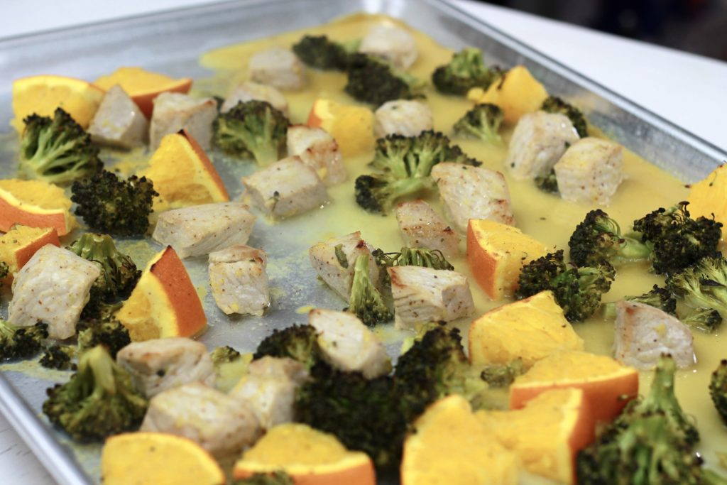 Cooked chicken, broccoli, and diced oranges all in one pan ready to be served.