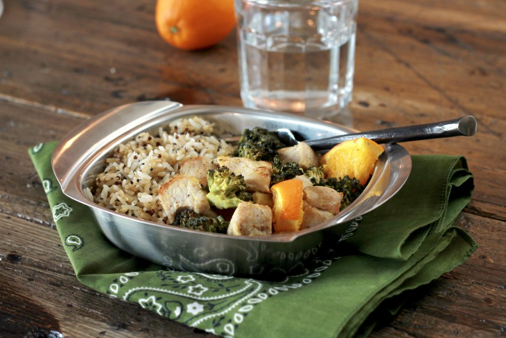 Orange chicken, with broccoli, and cooked diced oranges served with a side of brown rice in a silver dish ready to be eaten.
