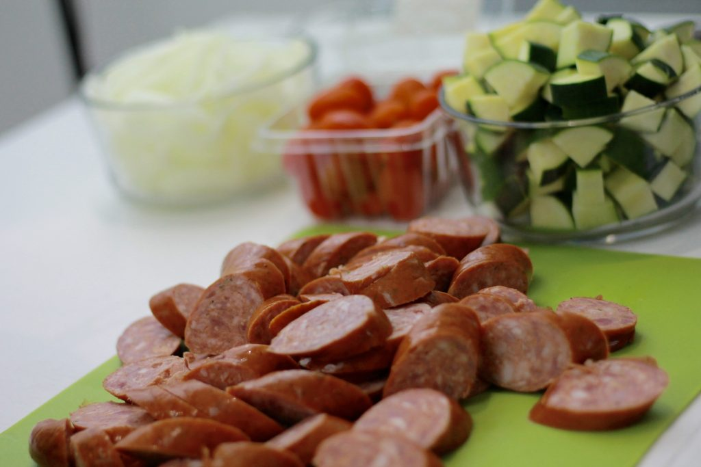 Uncooked sliced sausage on a cutting board, a bowl of diced zucchini, with petite tomatoes and chopped onions.