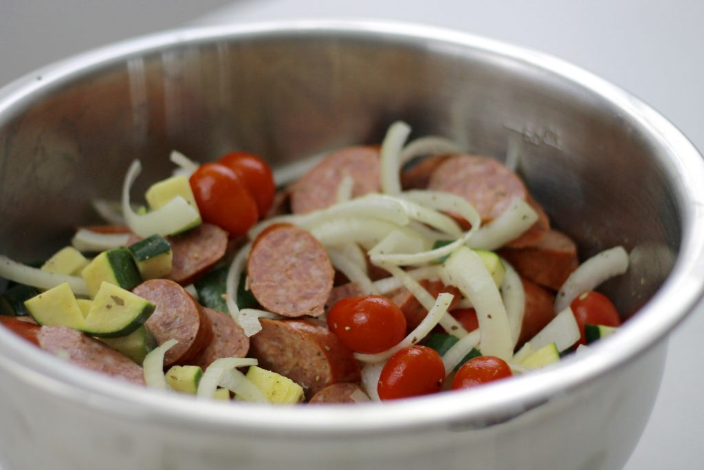 Sliced sausage, diced zucchini, petite tomatoes and chopped onions all in a bowl ready to be mixed.
