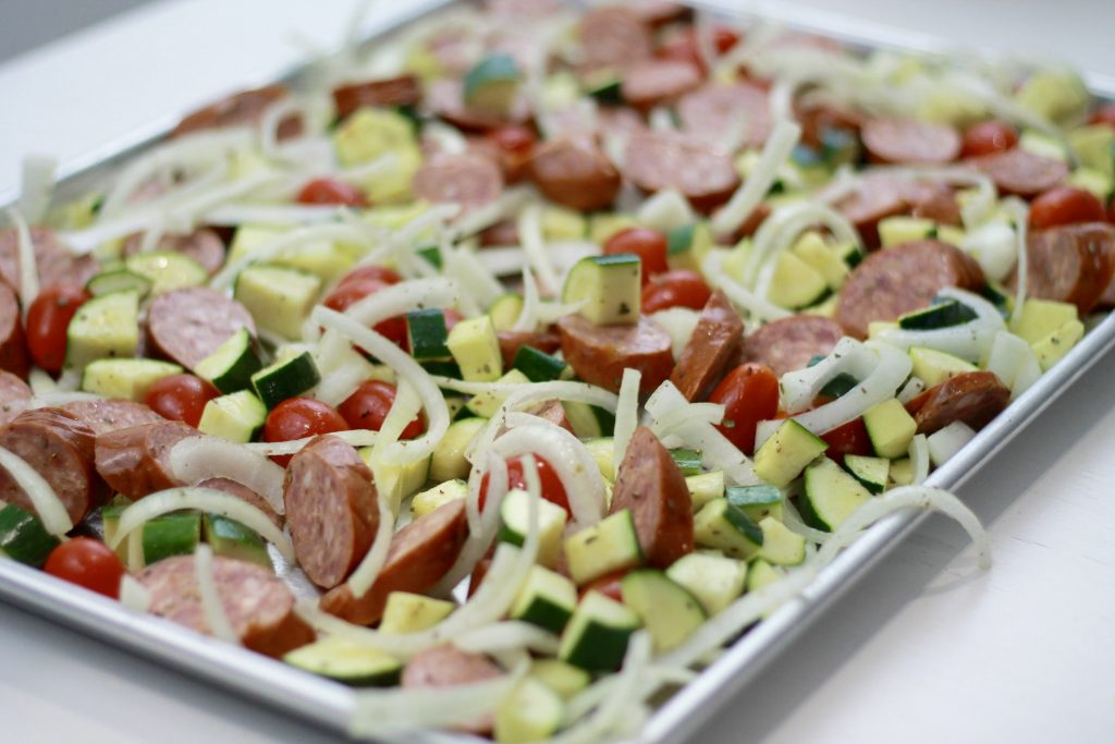 One pan of sausage diced zucchini, petite tomatoes and chopped onions ready to be placed in the oven.