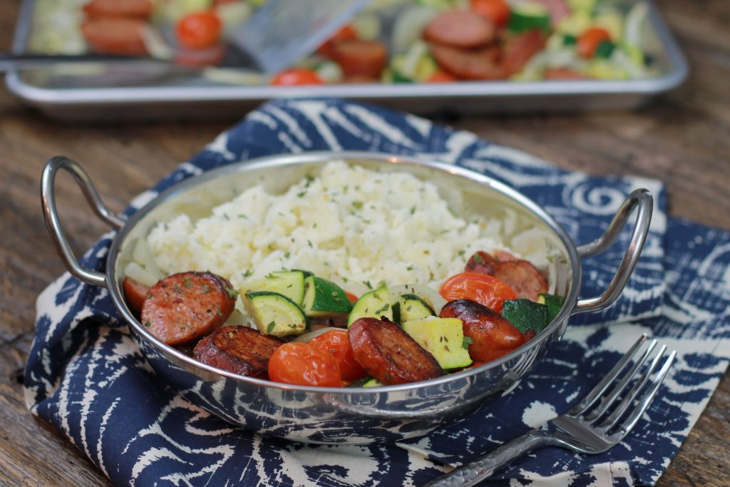 Sausage, zucchini, petite tomatoes, and chopped onions served in a bowl with a side of white rice.