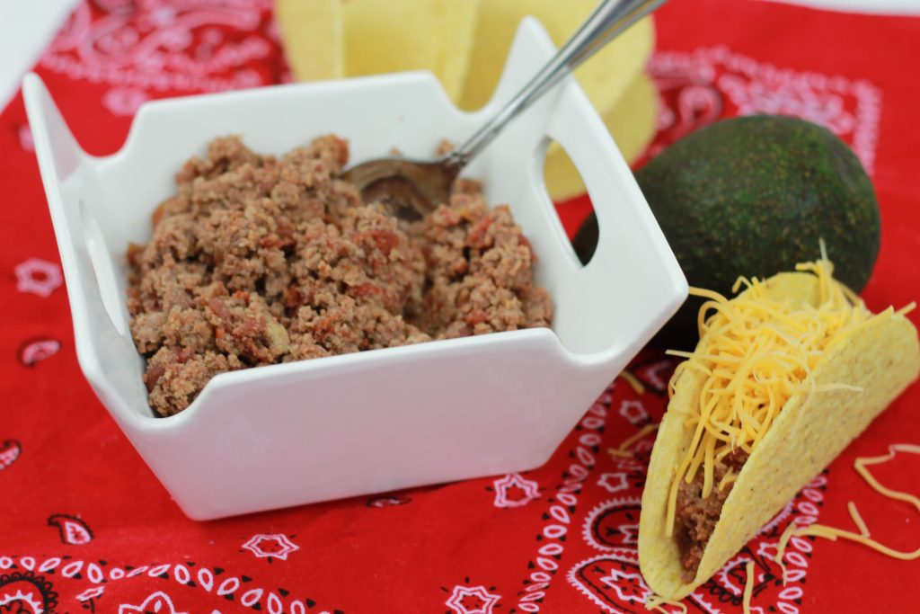 Seasoned cooked taco meat served in a white bowl scooped on a hard corn tortilla shell topped with shredded cheese.