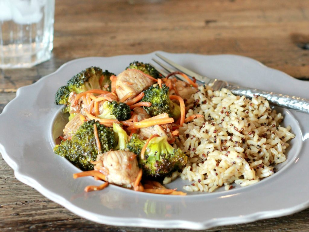 Oven baked chicken, broccoli, and sliced carrots all served on a plate with a side of brown rice.