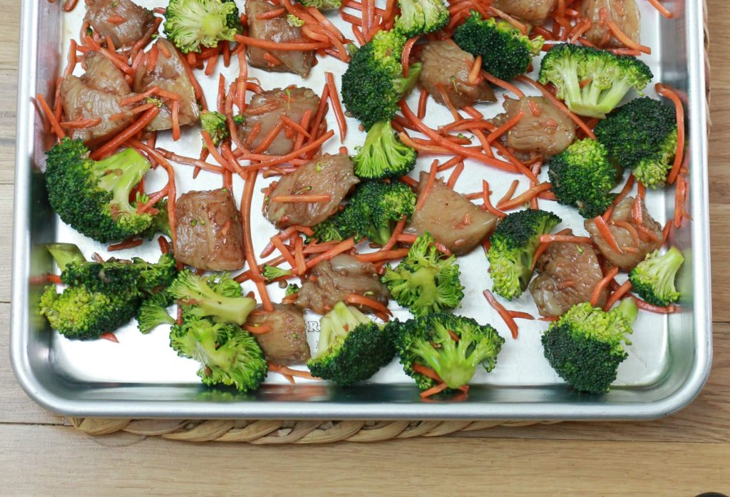 Chicken, broccoli, and sliced carrots all on one pan ready to be cooked.