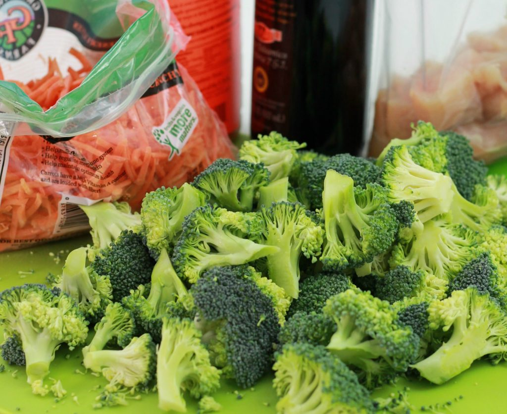 A bag of sliced carrots, and a pile of broccoli on a cutter board.