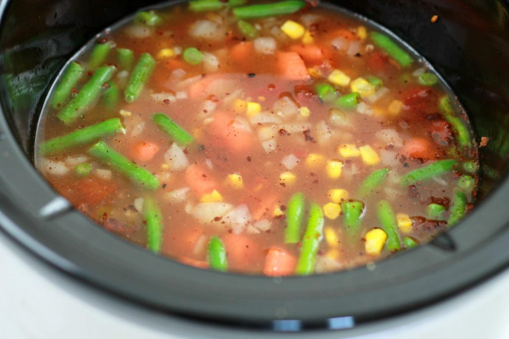 Green beans, chopped onions, diced tomatoes, with added broth, and frozen corn all mixed together and placed in a crock pot.