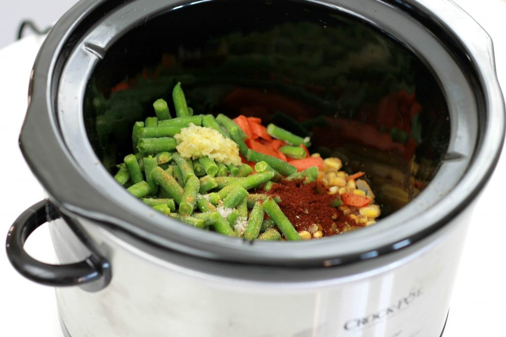 Green beans, chopped onions, diced tomatoes, and frozen corn all mixed together and placed in a crock pot ready to be cooked.
