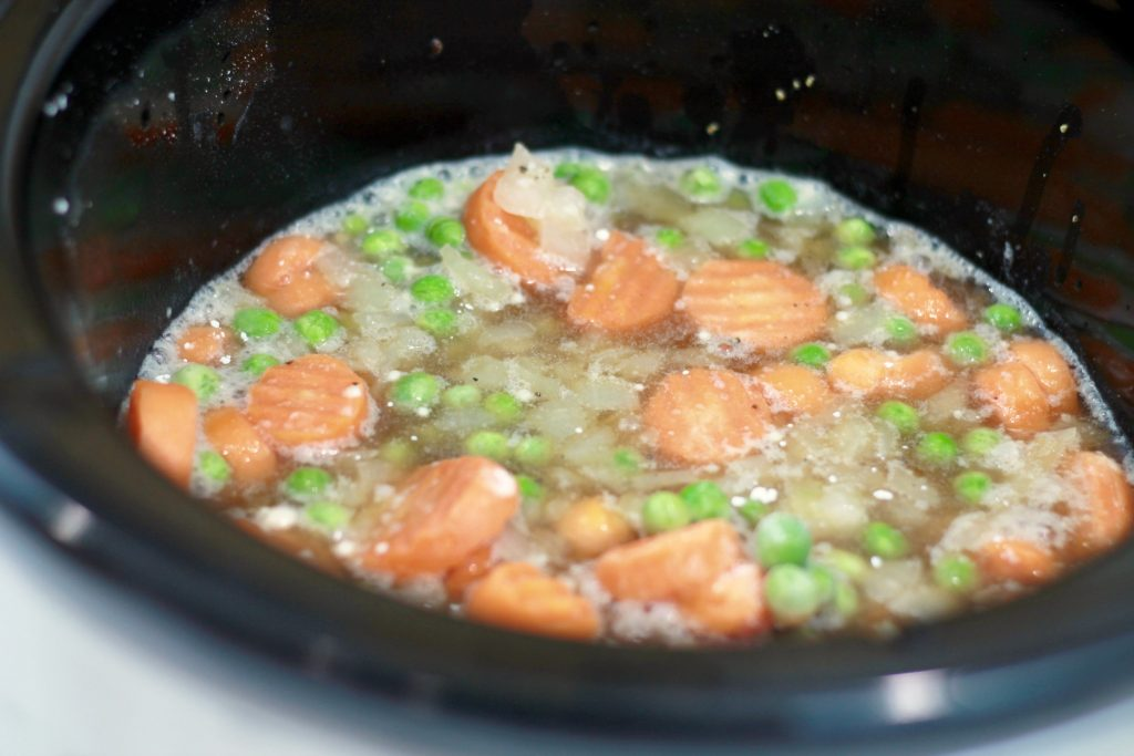 Peas, sliced carrots, diced potatoes, ad broth all boiling in a crockpot.