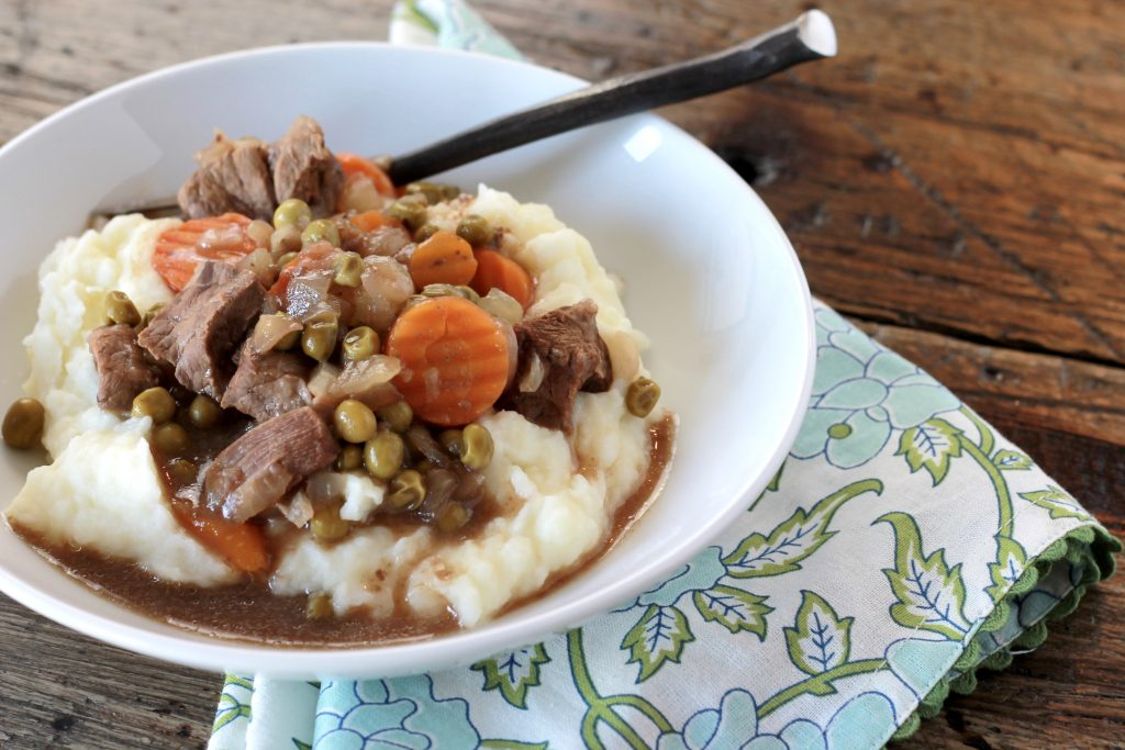 Steak bites, sliced carrots, peas, served on top of mashed potatoes in a white bowl ready to be eaten.