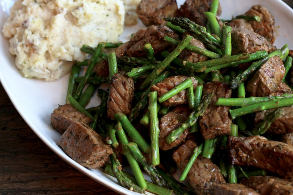 Spicy steak bites and asparagus on a white dish served with mashed potatoes