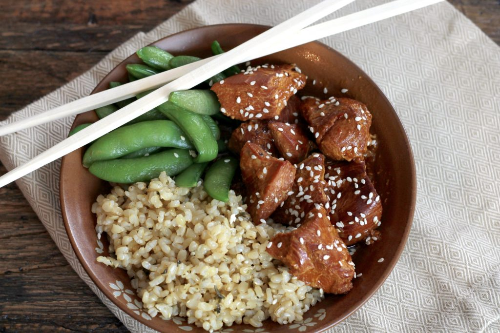 Honey seared chicken topped with seeds served with a side of brown rice, and edamame in a brown bowl ready to be served.