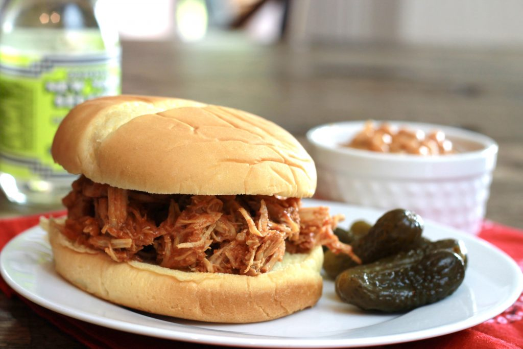 Shredded BBQ pork served in a hamburger bun with pickles, and a side of baked beans ready to be eaten.