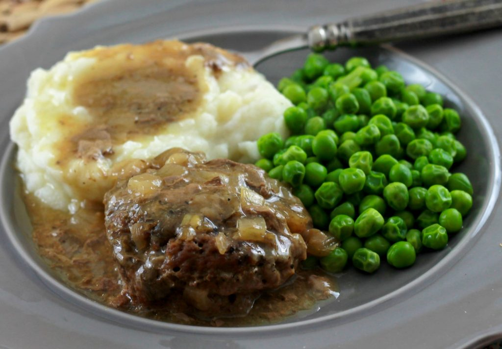 Salisbury steak with brown gravy on a gray plate served with mashed potatoes and green peas