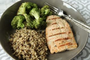 Grilled salmon on a round gray plate, served with brown rice and broccoli.