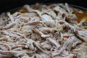 Shredded chicken in a slow cooker prepared for sour cream chicken enchiladas.