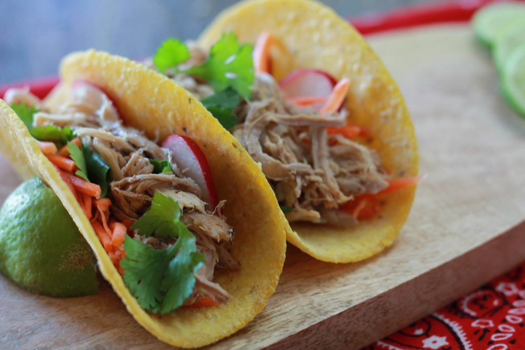 Two shredded pork carnitas tacos in corn tortillas served with cilantro and lime.