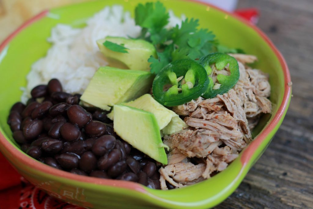 Shredded pork carnitas served in a green bowl with white rice, black beans, chopped avocados, and sliced jelopanos.