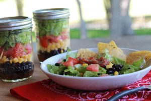 Glass jars with lids containing black beans, corn, tomatoes and salad. White plate with the salad mixed and chips.