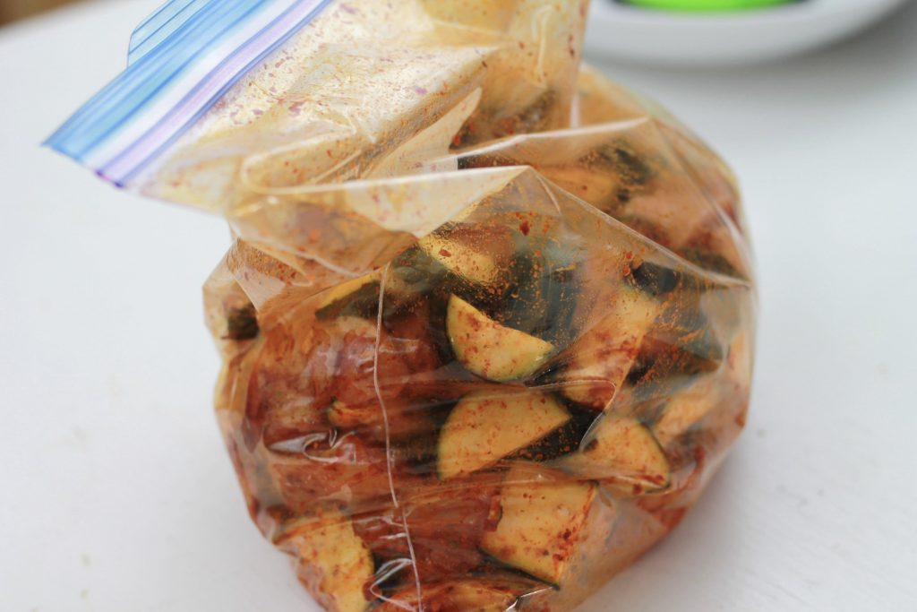 Cucumber, chicken, and spices all mixed together in a clear plastic bag.