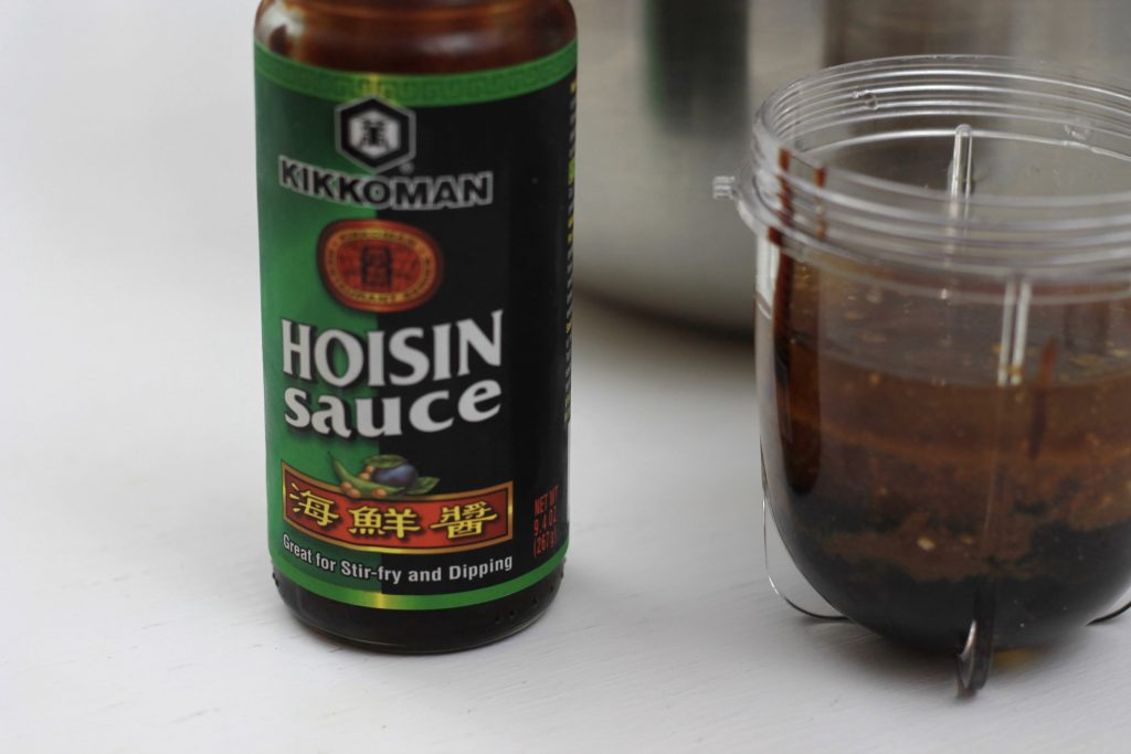 A bottle of Hoison sauce and a plastic conditioner with hoisin sauce ready to be blended.