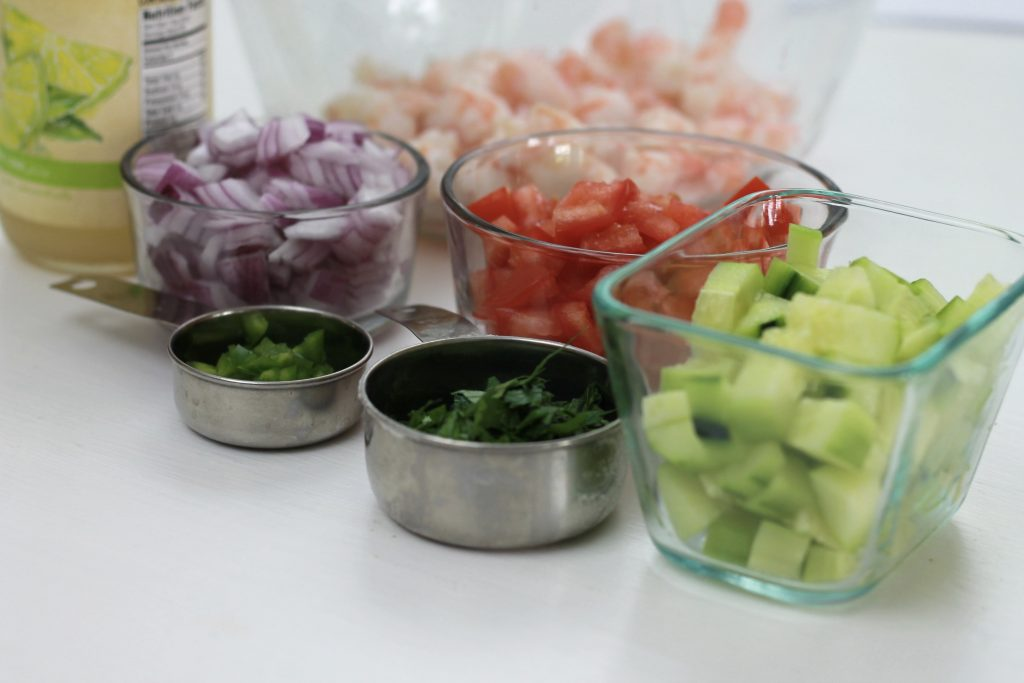 Chopped celery, onions,cilantro, chives,tomatoes placed in individual bowls, along with shrimp and a bottle of lime juice, all ready to be mixed together.
