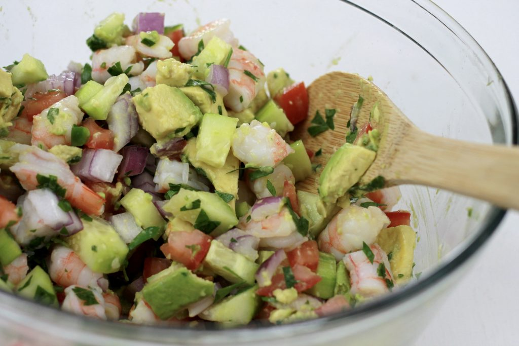 Shrimp, avocado, chopped onions, tomatoes, chives, and cilantro, all being mixed together in a clear bowl.