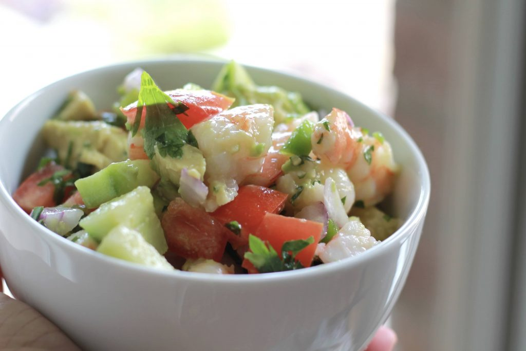 Shrimp, avocado, chopped onions, tomatoes, chives, and cilantro, all mixed together, served in a white bowl.