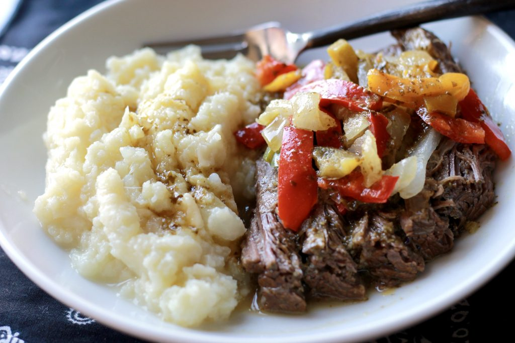 Cooked flank steak topped with onions, bell peppers, and vegetables, served on a white plate with a side of cauliflower mashed potatoes.