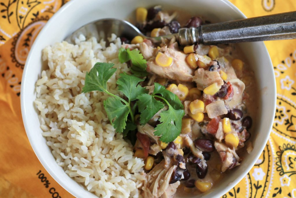 Cooked diced chicken mixed with corn, onions, tomatoes and black beans served with a side of white rice topped with cilantro all in white bowl .