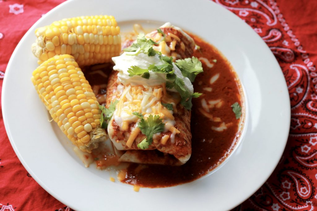 Slow cooked beef burrito wrapped in a four tortilla, bathed in enchilada sauce, topped with shredded cheese an lettuce, with a side of two petite ears of corn all served on a white plate.