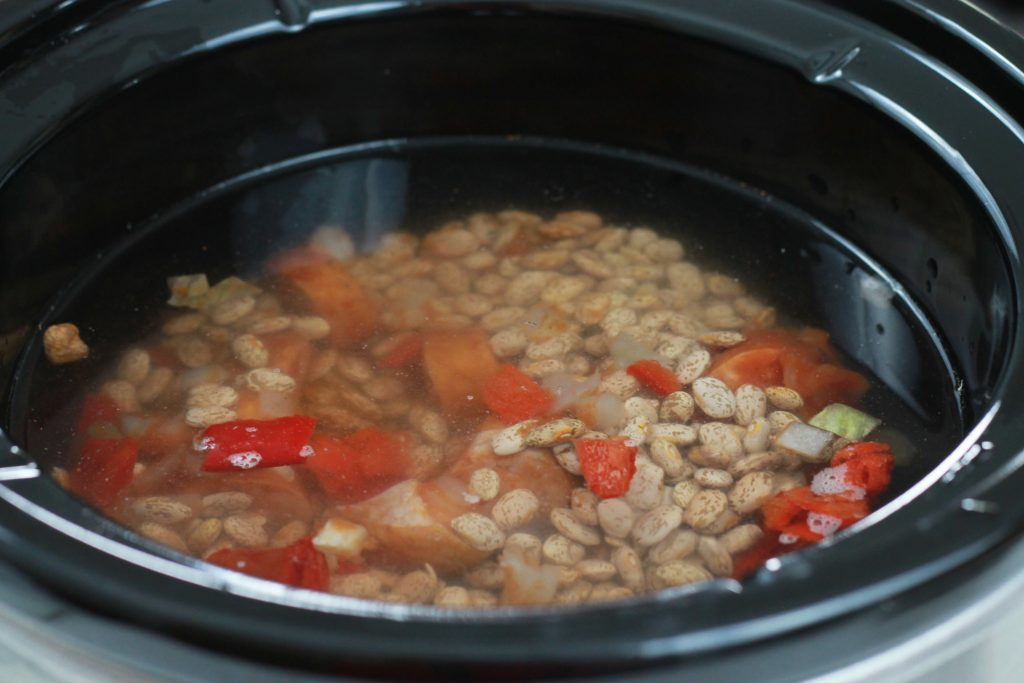 Sliced sausage, mixed with beans, sliced bell peppers, chopped onions, and water in a crockpot ready to be cooked.