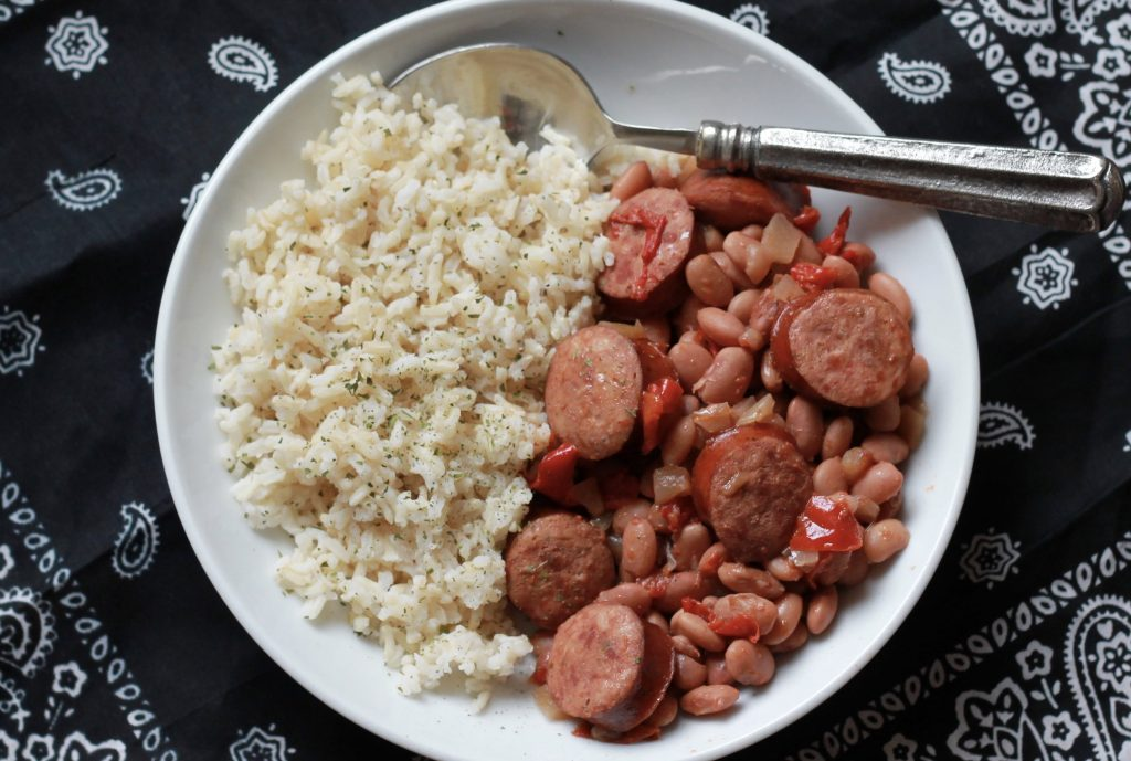Slow cooked sausage, beans, red bell peppers, served with a side of white rice on a white plate.