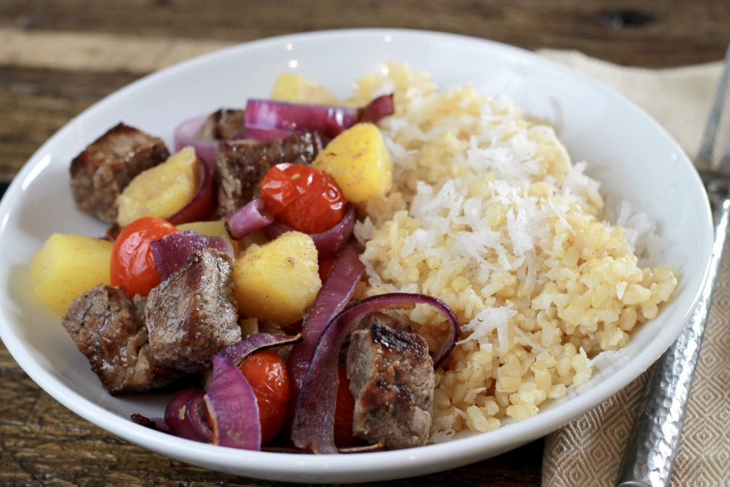 Beef, allspice seasoning, chopped red onion, pinnacle chunks, 5th seasoning, and red petite tomatoes served in a white bowl with a side of white rice.