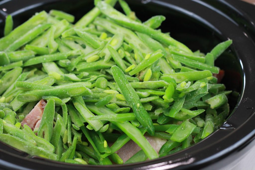 Frozen fresh cut green beans placed on top of ham in a black crock pot