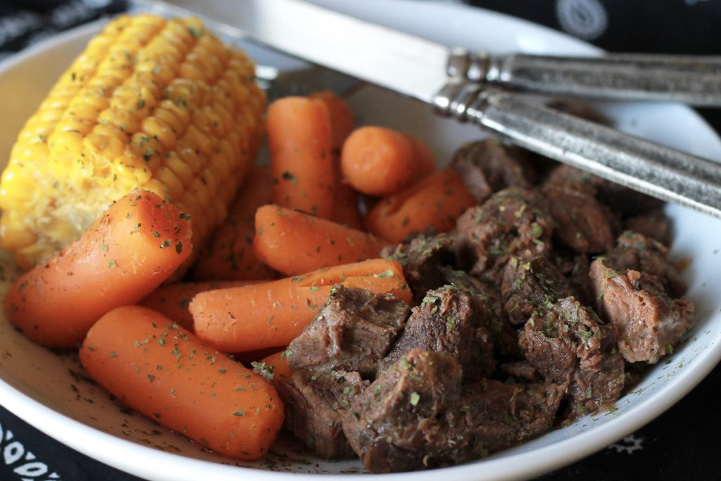 Cooked seasoned chopped steak, served with a side of slow cooked carrots and a petite ear of corn,all served on a plate.