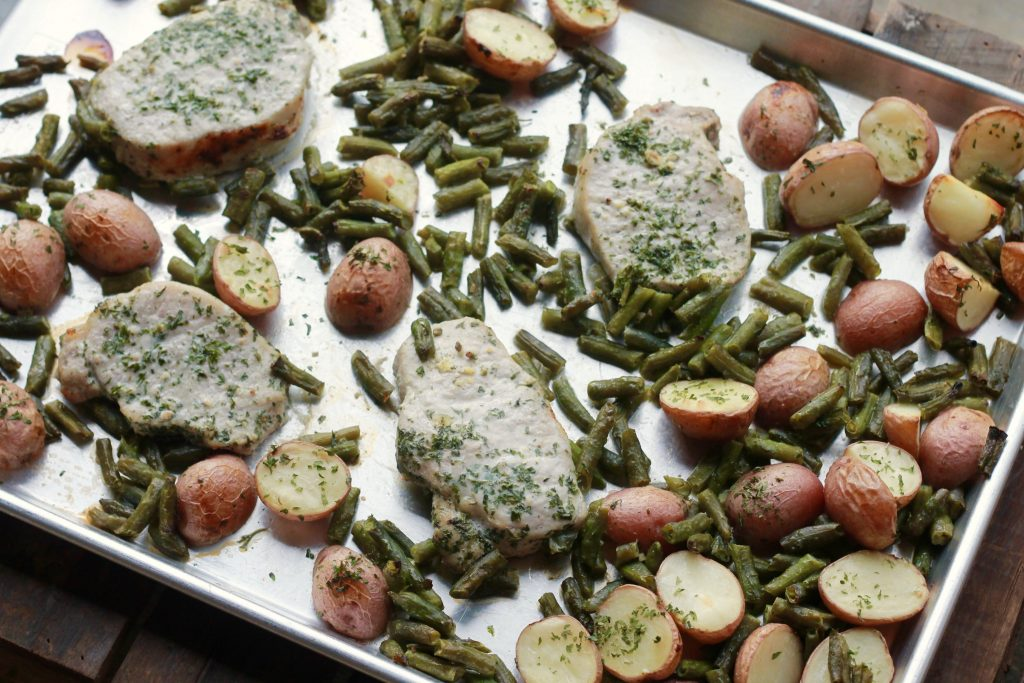cooked pork chops with diced red potatoes and green beans seasoned with ranch mix all in one silver pan.
