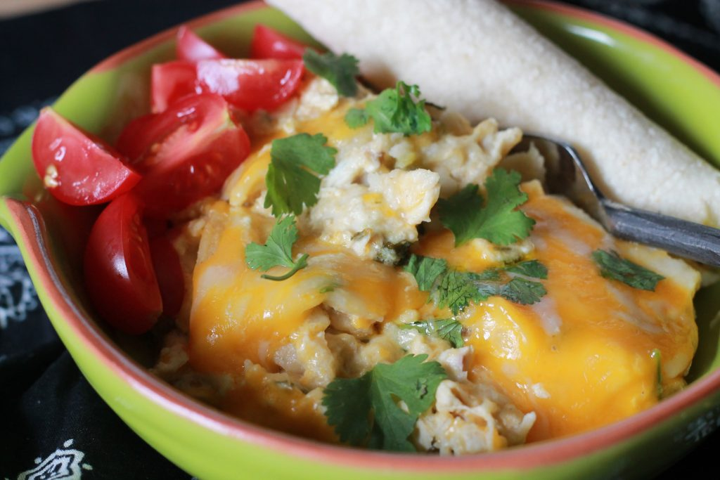 slow cooker sour cream enchilada casserole, served with diced tomatoes, melted cheese, cilantro, and a corn tortilla, in a green bowl with a silver fork on a blue bandana.