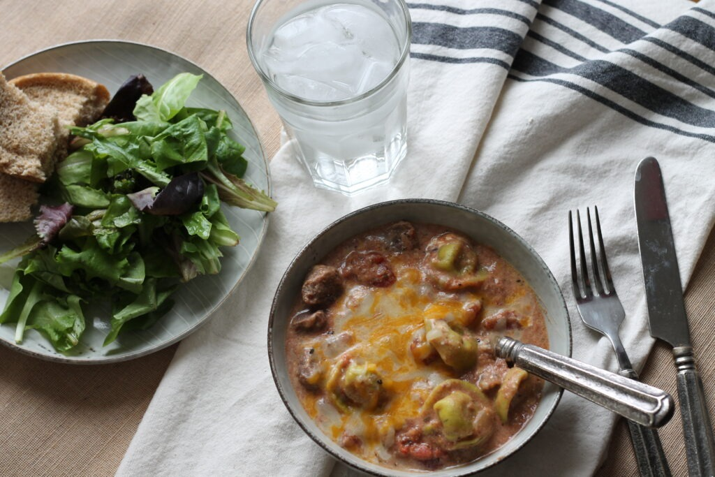 Cheesy beef tortellini soup with melted cheese salad and glass of water