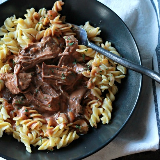 slow cooked beef with creamy tomato sauce seasoned sauce served on top of cooked pasta in a black bowl.