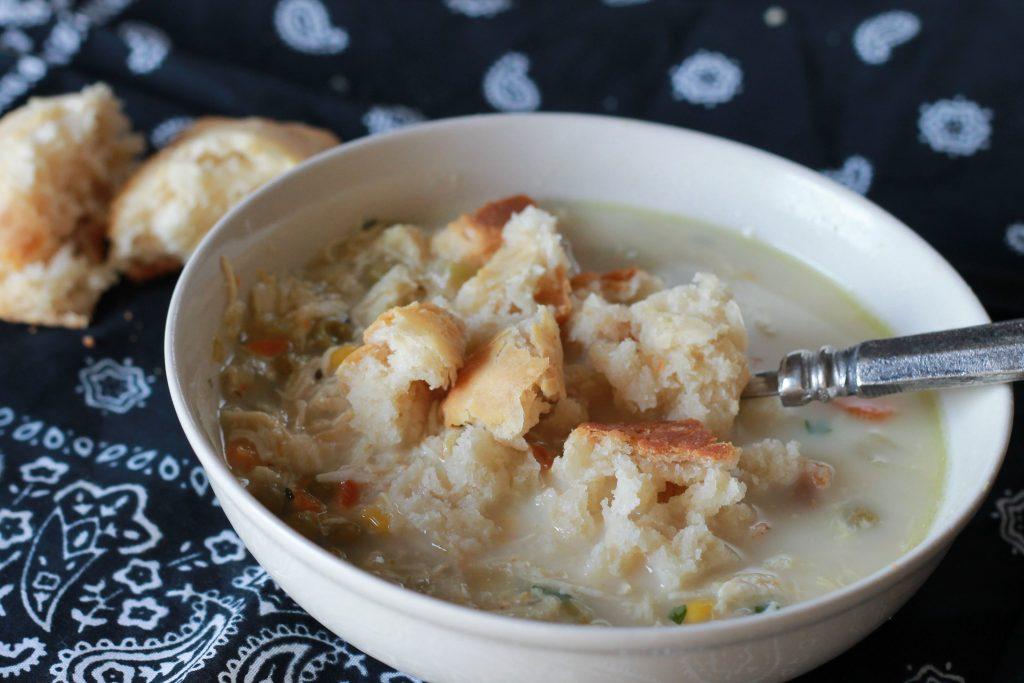 slow cooked chicken with chopped carrots, corn and broth mixed with greek yogurt to create a creamy chicken pot pie soup topped with crumbled biscuits, and with a side of biscuits.